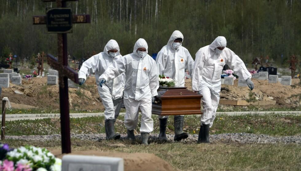 Nok en coronadød russer blir begravet på en kirkegård i St. Petersburg mens familien står på god avstand. Foto: Dmitri Lovetsky/AP/ NTB