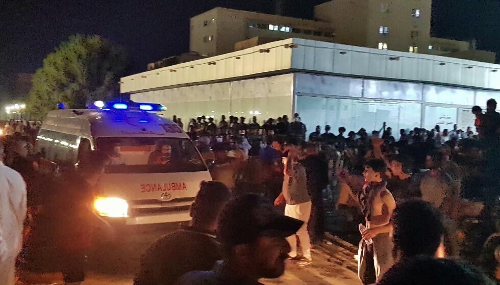 Demonstranter samlet seg utenfor Al-Hussein-sykehuset i byen Nasiriya tidlig tirsdag morgen. Nattens brann er den andre dødelige sykehusbrannen i Irak i år. Foto: AP / NTB.