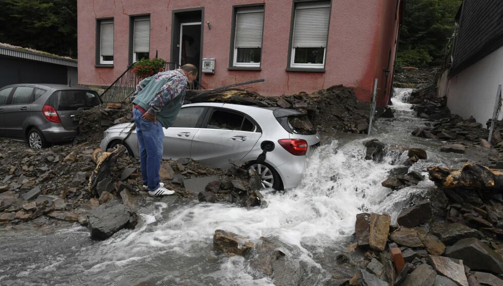 En mann kikker på bilen sin i Hagen i Tyskland, etter at flommen har herjet. Foto: NTB