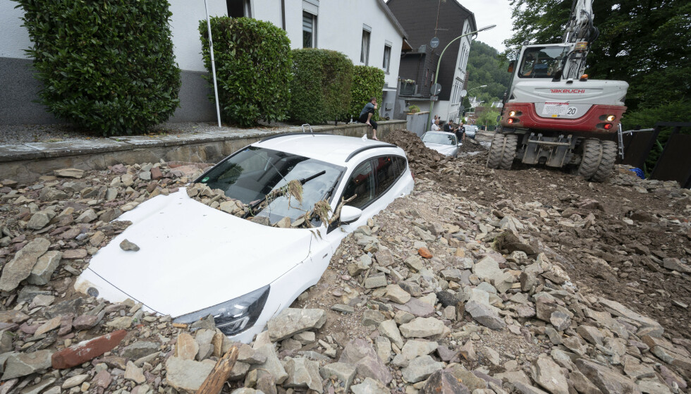 En bil er begravet i masser etter flom i Hohenlimburg-området i Hagen i Tyskland torsdag. Ødeleggelsene er store. Foto: Julian Stratenschulte / AP / NTB