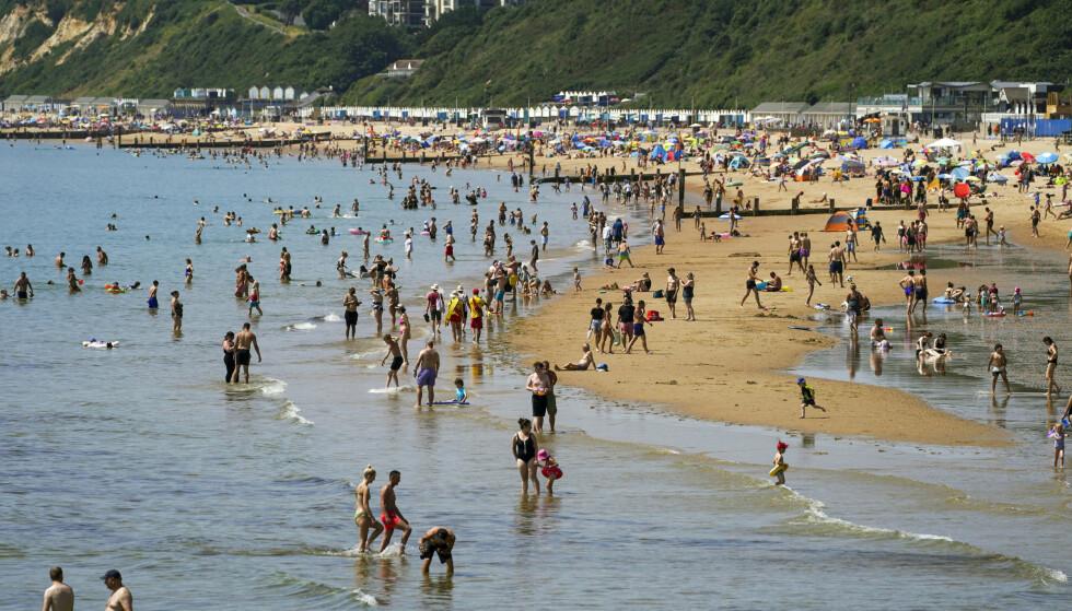 Varmt vær trakk mange til Bournemouth-stranda i Dorset sørvest i England mandag. Foto: Steve Parsons/PA via AP / NTB