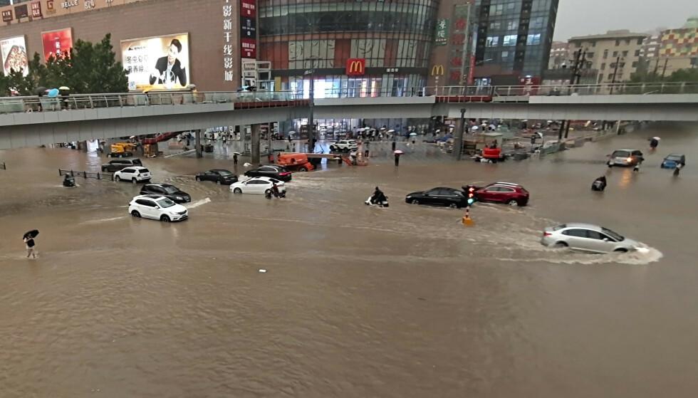 Biler står fast under oversvømmelsene forårsaket av kraftig regnvær i millionbyen Zhengzhou sentralt i Kina tirsdag. Foto: Chinatopix Via AP / NTB