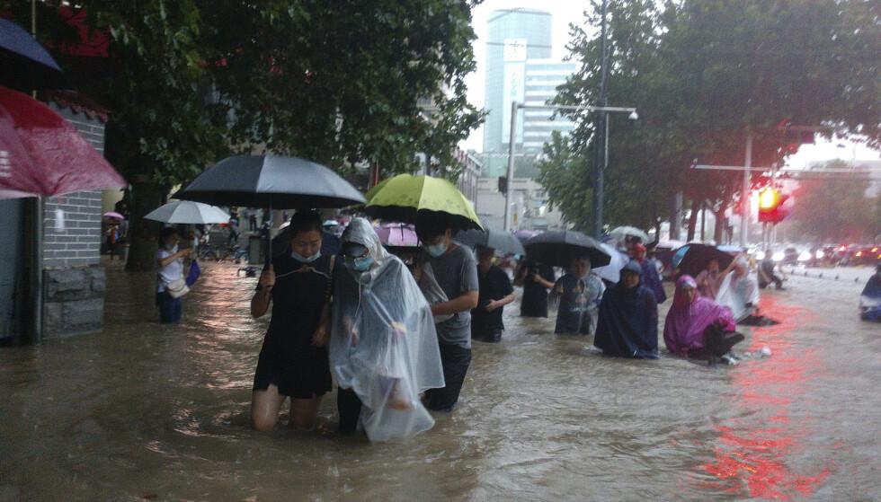 Folk beveger seg gjennom flomvannet etter kraftig nedbør i byen Zhengzhou med over ti millioner innbyggere. Foto: Chinatopix Via AP / AP / NTB