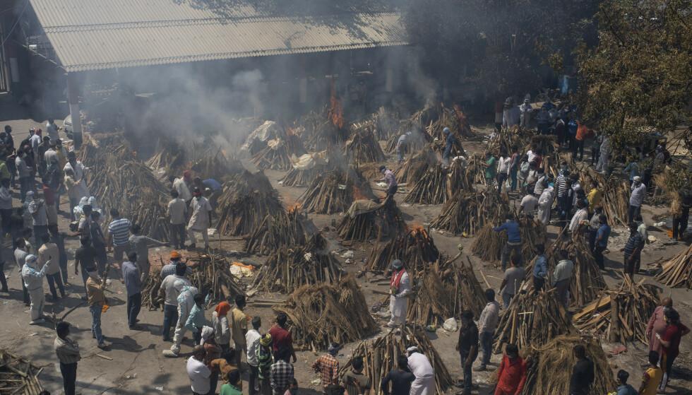 Bilde fra New Delhi i april i år, der et større antal begravelses-bål blir tent. De som kremeres her, var coronaofre. Foto: NTB