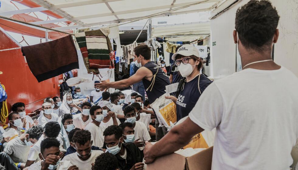 Tidligere i juli fikk «Ocean Viking» legge til kai på Sicilia i Italia med 573 migranter om bord. Her deler mannskapet ut mat mens de fortsatt søkte en havn. Arkivfoto: Flavio Gasperini/SOS Méditerranée via AP/NTB