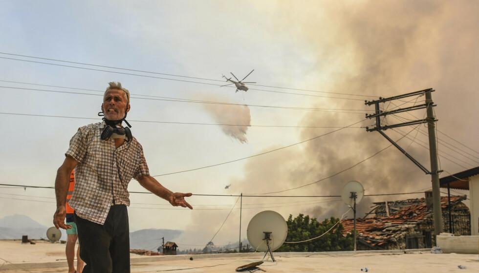 Et helikopter slipper vann over Sirtkoy i Antalya søndag. Skogbrannene i Tyrkia har siden onsdag krevd minst åtte menneskeliv og ført til massive ødeleggelser. Foto: AP/NTB