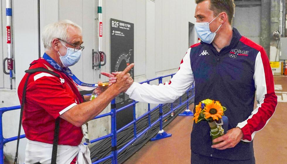 Karsten Warholm viser OL-gullmedaljen til trener Leif Olav Alnes etter medaljeseremonien tirsdag. Foto: Lise Åserud/NTB