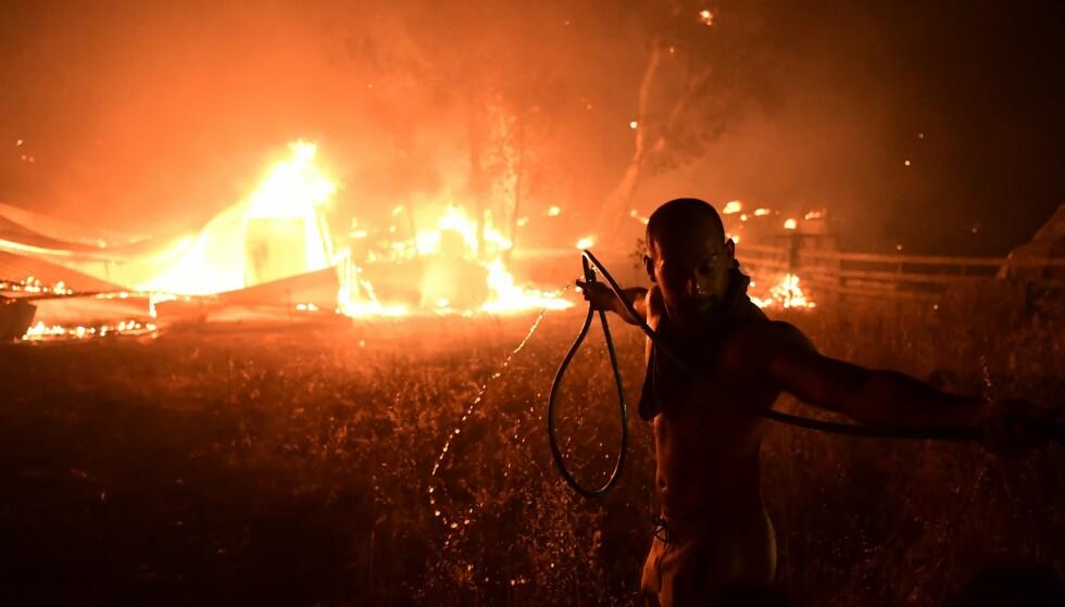 En mann kjemper mot skogbrannen med en hageslange i området Adames nord i Aten natt til onsdag. Flere tusen personer har flyktet fra hjemmene sine. Foto: Michael Varaklas, AP / NTB