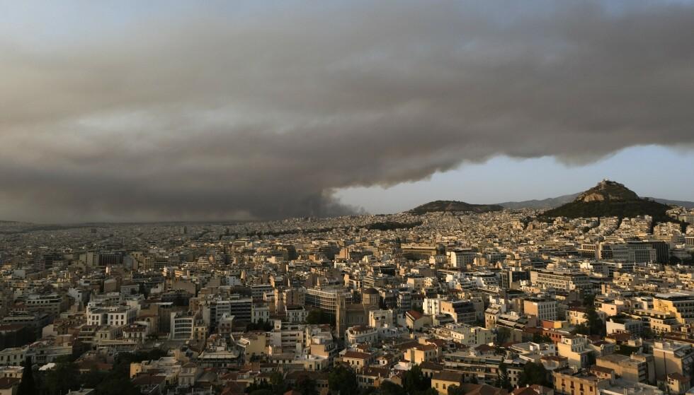 Røyk fra skogbrannen veltet innover Aten tirsdag. Foto: Aggelos Barai, AP / NTB