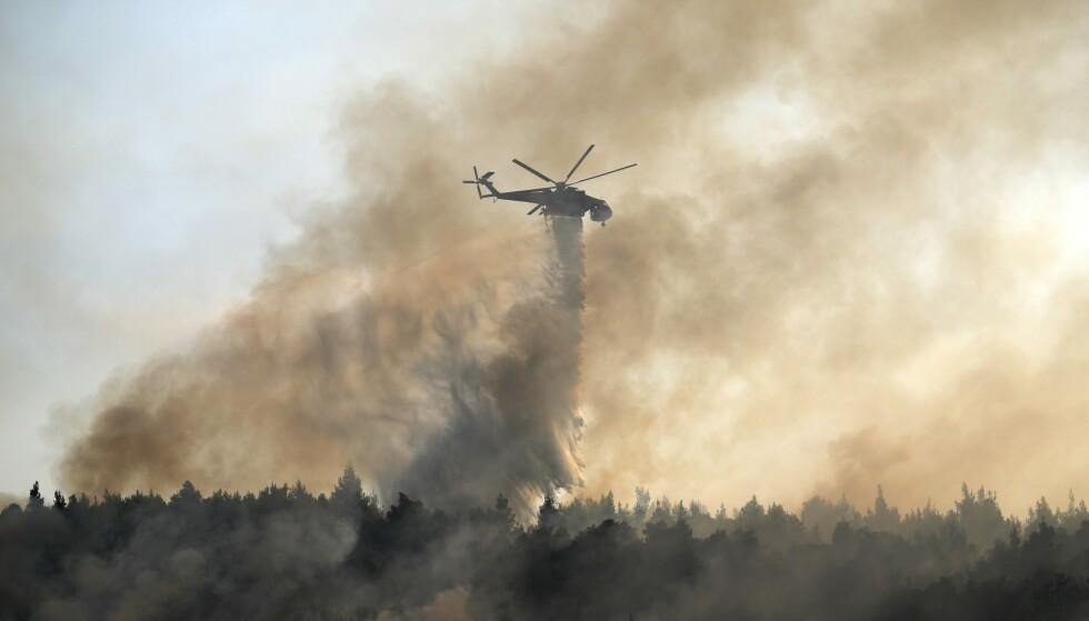 Det ble sent ut to brannfly fra Kypros - her slipper et helikopter vann over brannen i Varibobi -området som ligger i Nord -Athen. Foto: Thanassis Stavrakis, AP/NTB.