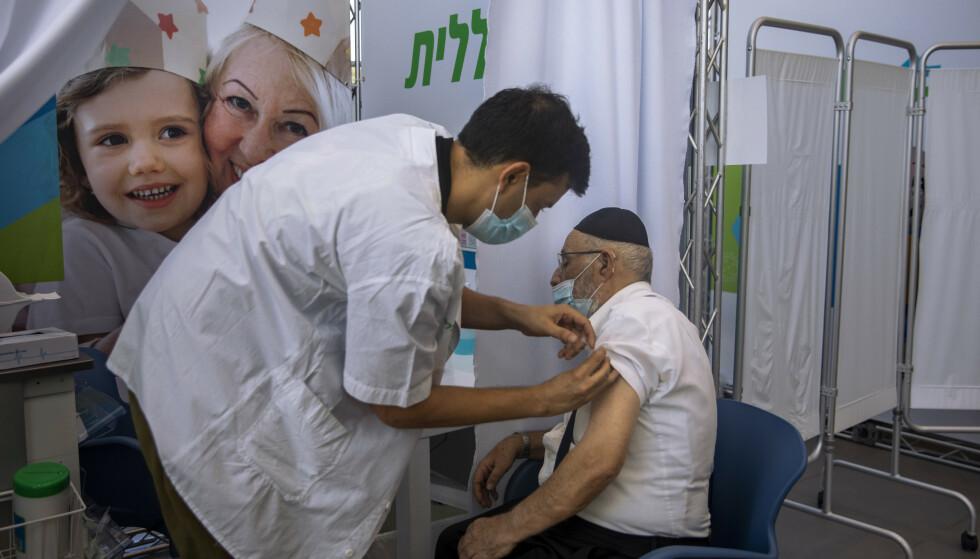 En mann mottar en tredje dose med Pfizer i Tel Aviv. Foto: Oded Balilty / AP / NTB