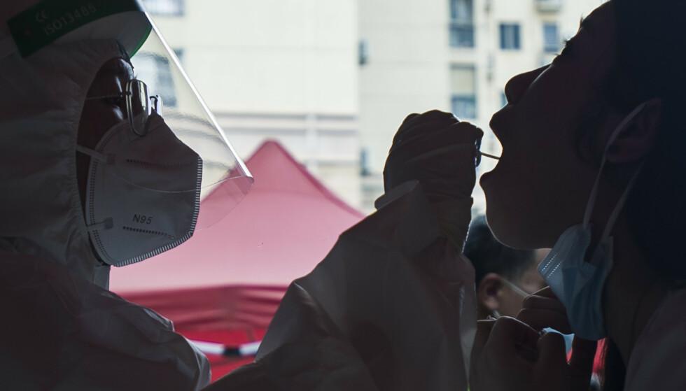 En kvinne testes for korona i Wuhan tidligere denne måneden. Det var i denne kinesiske storbyen at koronapandemien begynte i slutten av 2019. Foto: Chinatopix / AP / NTB