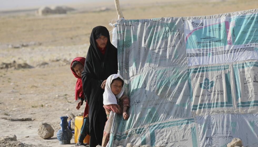 En kvinne og hennes to døtre står foran et telt i en leir for internt fordrevne i Afghanistan. Foto: Rahmat Gul / AP / NTB