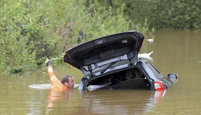 Det voldsomme regnet i natt førte til flom og store problemer i Sverige. Her jobber en mann med en bil som har havnet i vannet på Källviksvägen i Falun. Flere andre veier står også under vann. Foto: Ulf Palm/TT / NTB