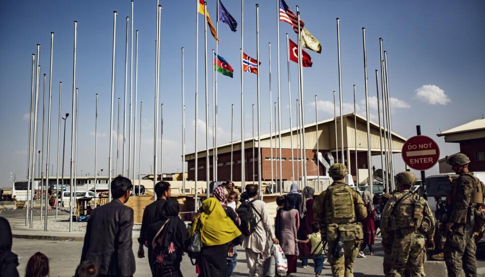 Amerikanske soldater følger en gruppe mennesker til terminalen på flyplassen i Kabul mandag. Foto: Mark Andries / U.S. Marine Corps / AP / NTB