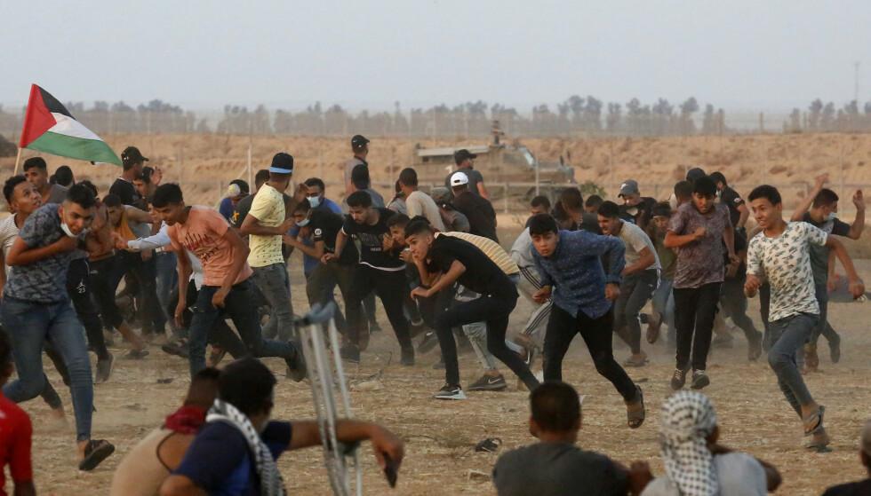 Demonstranter løper og forsøker å beskytte seg mot tåregass som israelske soldater avfyrer ved grensegjerdet mellom Israel og Gazastripen ved Khan Younis sør i den palestinske enklaven. Bildet ble tatt onsdag. Foto: Abdel Kareem Hana / AP / NTB