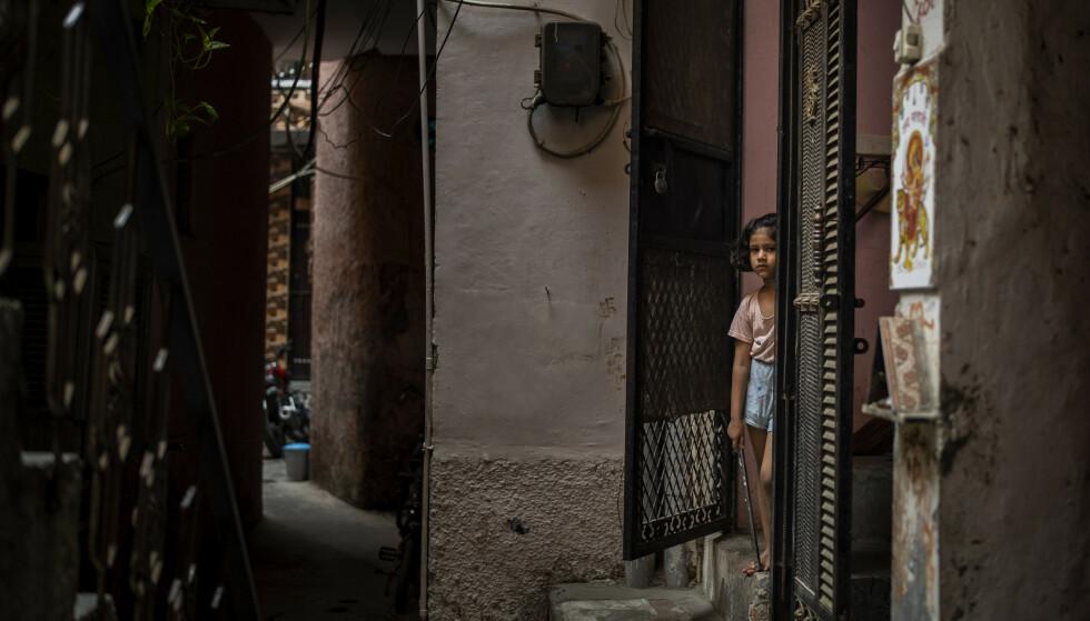 Den ni år gamle jenta bodde i huset ved siden av inngangen der jenta står, i et fattig område av New Delhi. Nå er fire menn, blant dem en 53 år gammel prest, tiltalt for voldtekt og drap. Foto: Altaf Qadri / AP / NTB