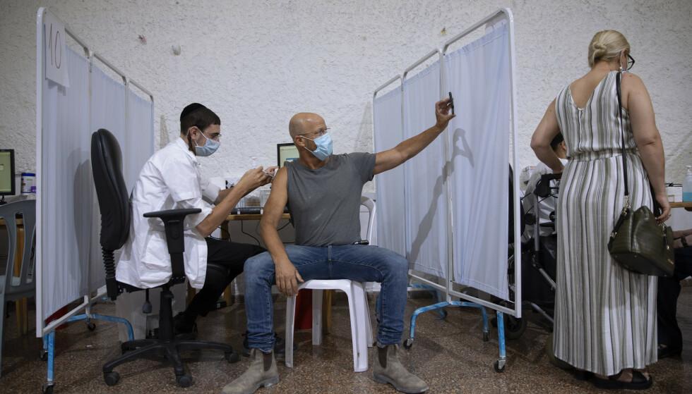 En israelsk mann tar en selfie mens han mottar en tredje dose med Pfizer-vaksine på et vaksinesenter i Ramat Gan i Israel mandag. Tallet på antall smittede var tirsdag nesten 11.000 nye tilfeller. Foto: Oded Balilty/ AP/ NTB
