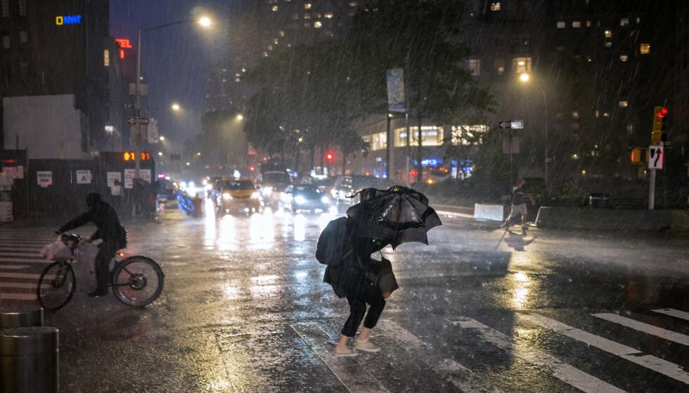 Folk krøker seg sammen for å krysse gata ved Columbus Circle på Manhattan mens stormen sto på som verst onsdag kveld. Foto: Craig Ruttle / AP / NTB