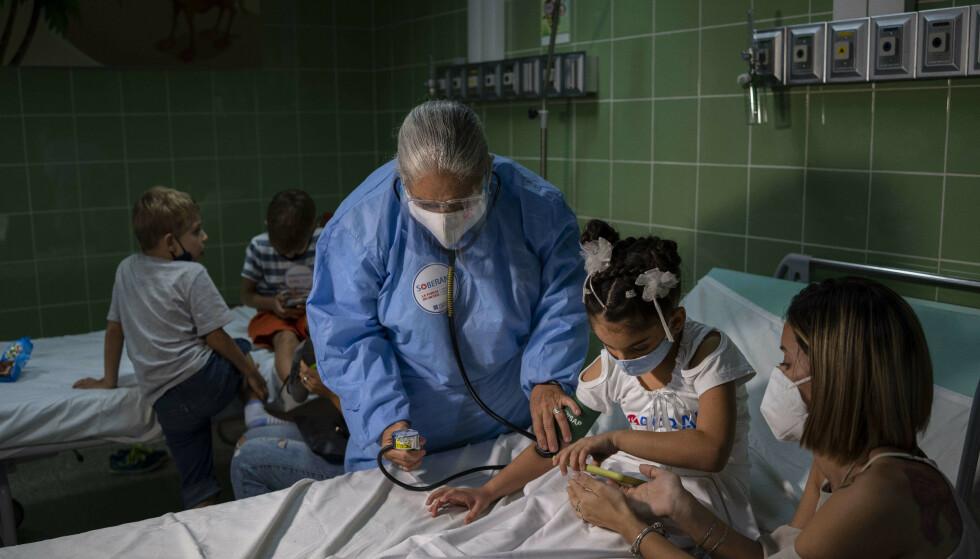En sykepleier måler blodtrykket etter å ha gitt ei jente den cubanske Soberana-vaksinen. Foto: Ramon Espinosa / AP / NTB