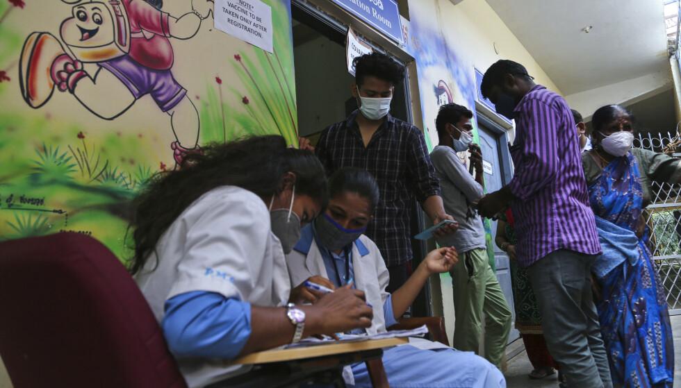 India er blant flere land som er hardt rammet av koronapandemien. På bildet blir folk registrert før de får koronavaksine på et senter i Bangalore. Foto: Aijaz Rahi / AP / NTB