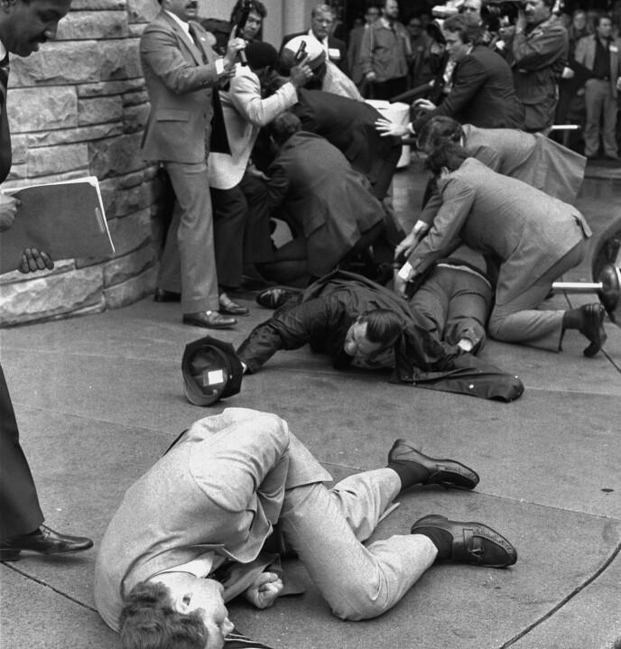 Secret Service-agenten Timothy J. McCarthy ligger såret på bakken i forgrunnen, mens president Ronald Reagans pressetalsmann James Brady ligger såret i bakgrunnen. Arkivfoto: Ron Edmonds / AP / NTB