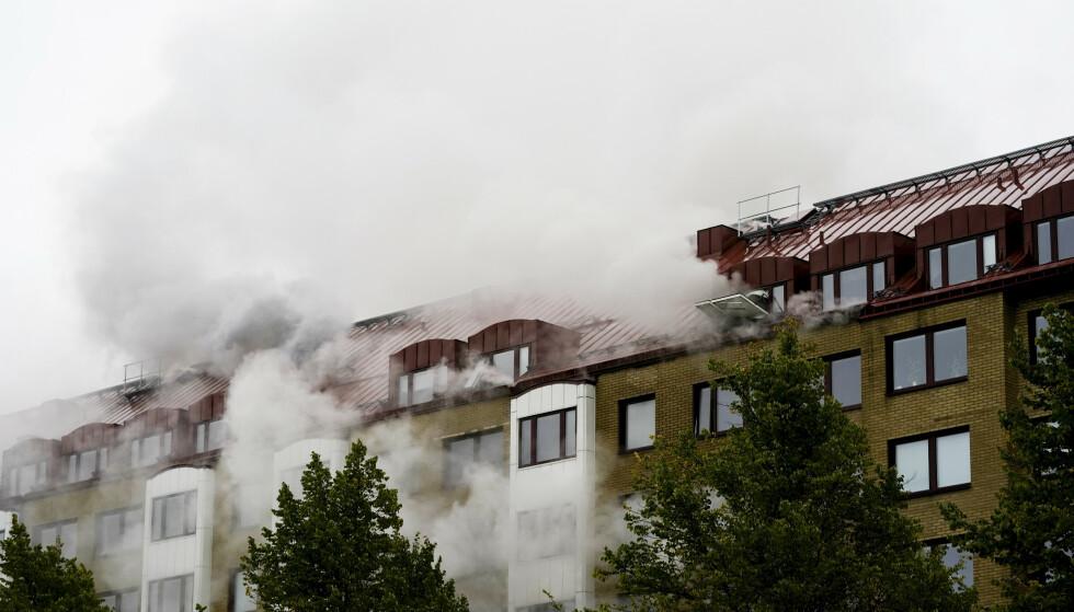 Eksplosjonen i en boligblokk i Annedal sentralt i Göteborg tirsdag forrige uke førte til en kraftig brann. En 55-åring er etterlyst i saken. Foto: Bjorn Larsson Rosvall / TT via AP / NTB