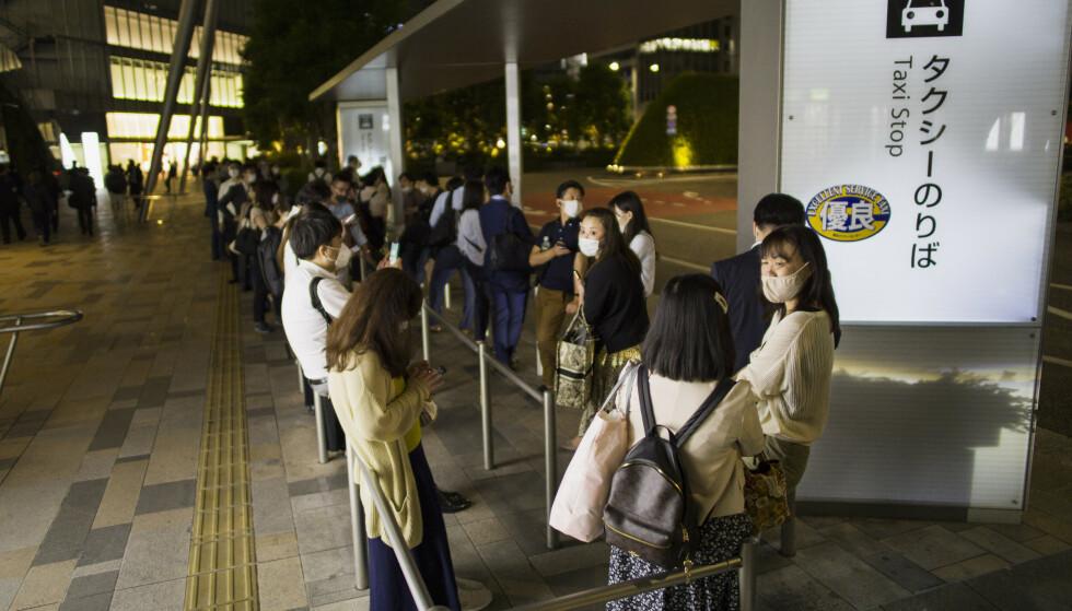Folk i taxikø utenfor en stasjon i Tokyo etter jordskjelvet torsdag. Metro- og togtrafikken ble stanset etter skjelvet. Foto: Hiro Komae / AP / NTB