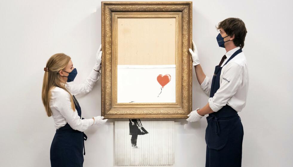 Det delvis ødelagte verket fra artisten Banksy selges igjen, under det nye navnet «Love is in the Bin». Foto: Dominic Lipinski / PA / AP / NTB